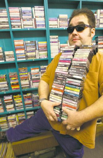 Jeff Bishop, owner of Sound Exchange carries an armful of audio cassettes. Bishop sells loads of cassettes to young hipsters who are looking for the next, old thing. With piles of cassettes that hipsters buy at a dozen at a time