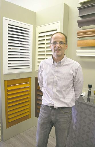 Budget Blinds owner Ron Hermann with a display of shutters at his store on Henderson Highway.