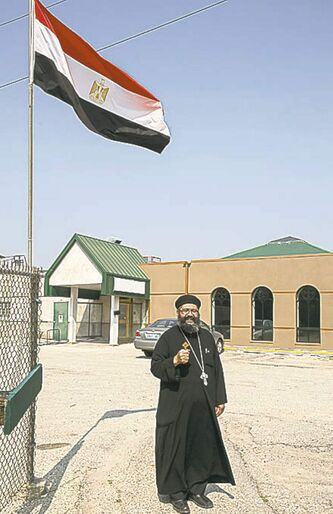 Coptic pastor Fr. Marcos Farag with the Egyptian flag Friday.