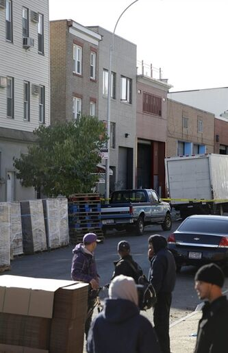 People stand near a row house, center, that was the location of a murder-suicide in the Brooklyn section of New York, Monday, Nov. 11, 2013. A musician shot and killed two members of an Iranian indie rock band and a third musician early Monday, and wounded a fourth person at their apartment before killing himself on the roof, police and the group's manager said. (AP Photo/Seth Wenig)