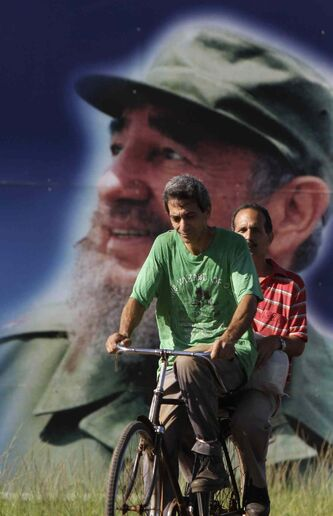 Men ride a bike past a large poster of Fidel Castro in the town of San Antonio de los Banos, Cuba.