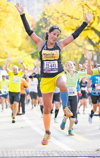 Christy Pasion of New York leaps across the finish line on Sunday.