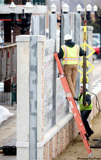 A city crew begins hoisting the panels for the flood wall along the Boardwalk in East Grand Forks on Monday.