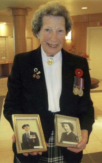 <p>SUPPLIED</p><p>Lynn, wearing her war medals, with a photo of husband Jim and an old photo of herself in uniform.</p>