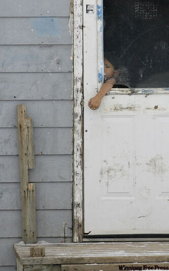 A child reaches through a broken window of a house in Pikangikum, a remote northern Ontario community.