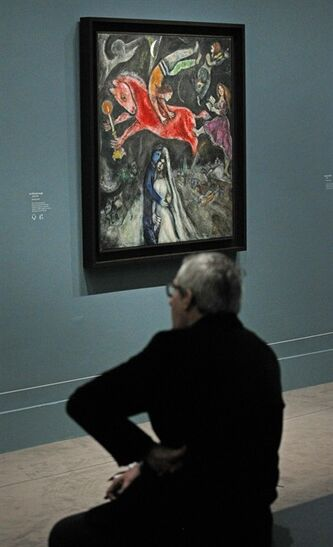 A member of the media sits next to 1944, Le Cheval Rouge, a painting by Russian artist Marc Chagall before the opening of the exhibition: Chagall, between War and Peace, at the Luxembourg museum in Paris, Tuesday Feb. 19, 2013. The exhibition starts February 21 and ends July 21, 2013.(AP Photo/Remy de la Mauviniere)