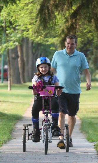 Ten-year-old Waverley Leduc rides her specially designed bike next to her dad, Jamie.