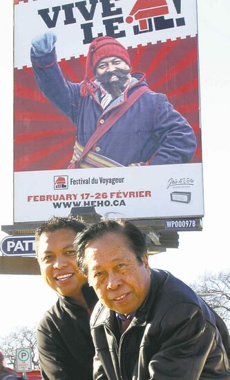 Ron Cantiveros and his father, Rod, in front of a billboard that features Ron as a voyageur.