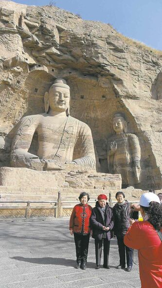 Tourists at the Yungang grottoes pose in front of huge statues of Buddha.
