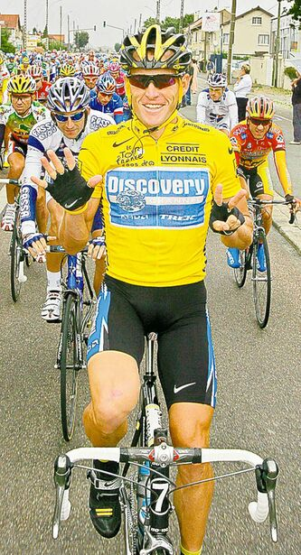 Lance Armstrong signals his seventh straight win in the Tour de France in 2005.
