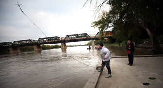 Volunteer Calvin Alexander hurls a home made grappling hook into the Red River Wednesday as a search for Missing and Murdered aborigional women got underway in Winnipeg.