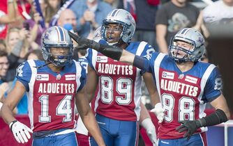 Montreal Alouettes' Brandon London (14) celebrates with teammates Duron Carter (89) and Dave Stala after scoring a touchdown against the Saskatchewan Roughriders during second half CFL football action in Montreal, Monday, October 13, 2014. THE CANADIAN PRESS/Graham Hughes