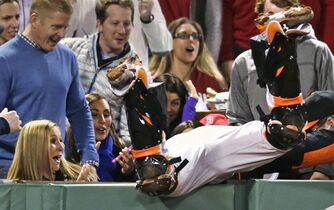 Baltimore Orioles catcher Caleb Joseph dives into the stands but cannot make the play on a foul ball hit by Boston Red Sox designated hitter David Ortiz during the eighth inning of a baseball game at Fenway Park in Boston, Friday, April 17, 2015. (AP Photo/Charles Krupa)