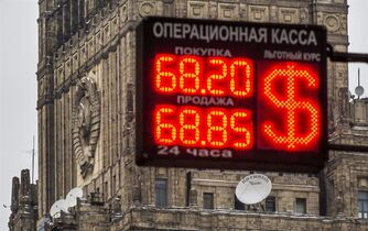 A sign at an exchange office with headquarters building of the Ministry of Foreign Affairs of the Russian Federation with the Soviet Sign in the background in Moscow, Russia, Thursday, Jan. 29, 2015. The Russian ruble extended its losses on Thursday, declining by 1.5 percent to 69 rubles against the dollar. (AP Photo/Alexander Zemlianichenko)
