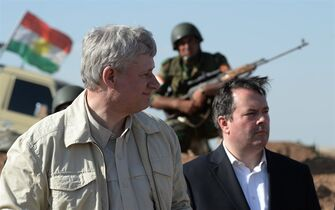 A Kurdish soldier sits in the background as Prime Minister Stephen Harper and Minister of Defence Jason Kenney visit members of the Advise and Assist mission, approximately 6 km from active ISIL fighting positions, 40 km west of Erbil, Iraq, on Saturday, May 2, 2015. THE CANADIAN PRESS/Sean Kilpatrick