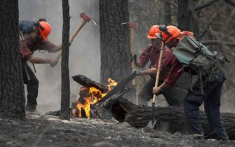 Firefighters tackle a flare up at the Smith Creek fire located on a hillside in West Kelowna, B.C., Saturday, July, 19, 2014. Manitoba is sending crews to British Columbia and the Northwest Territories to help battle forest fires there.