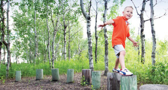 Charlie Baldock, 3, navigates a row of wood stumps at FortWhyte Alive.