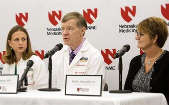 Dr, Angela Hewlett,, left, and Shelly Schwedhelm, right, Director of Emergency, Trauma and Preparedness, look on as Dr. Phil Smith, speaks to the media regarding Ebola patient Ashoka Mukpo, Wednesday, Oct 22, 2014 in Omaha, Neb. Mukpo, who contracted the virus while working in Liberia as a freelance cameraman for NBC and other media outlets, was released from Nebraska Medical Center's biocontainment unit early this Wednesday morning. (AP Photo/The World-Herald, Sarah Hoffman) MAGS OUT, TV OUT