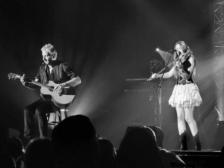 Graham Russell of Air Supply plays guitar while Winnipeg's Sierra Noble accompanies on her fiddle.