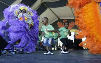 Tyrek Fair, 5, center left, and Mikheim Thompson, 5 dance onstage withThe Young Seminole Hunters Mardi Gras Indians at the New Orleans Jazz and Heritage Festival in New Orleans, Thursday, April 30, 2015. (AP Photo/Gerald Herbert)