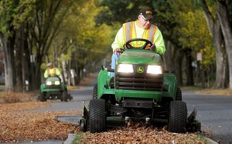 In this Sept. 30, 2014 photo, Westmont Borough Parks & Public Works crew member Tom Holbay uses a John Deere tractor to remove the fallen elm leaves from the median of Luzerne Street in Johnstown, Pa., while Jim Carbaug trails behind to clean up the rest. John Deere reports quarterly financial results on Wednesday, Nov. 26, 2014. (AP Photo/The Tribune-Democrat, Thomas Slusser)