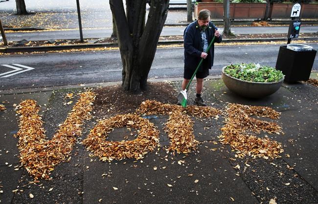 Tim Boyden uses the loose fall leaves in front of his business in Eugene, Ore., to encourage people passing by to vote in the midterm election.