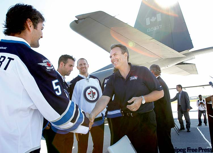 Winnipeg Jets GM Kevin Cheveldayoff shakes hands with defenceman Mark Stuart at the ceremony at 17 Wing Winnipeg.