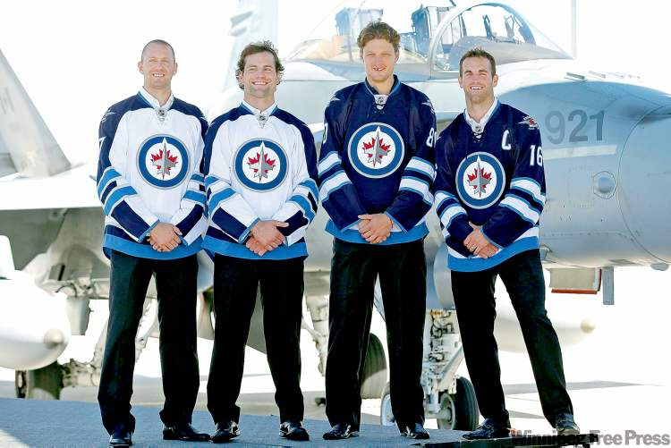 Winnipeg Jets Eric Fehr (from left), Mark Stuart, Nik Antropov and Andrew Ladd sport the new Jets jerseys during the unveiling ceremony at the 17 Wing Winnipeg Canadian Forces base Tuesday.