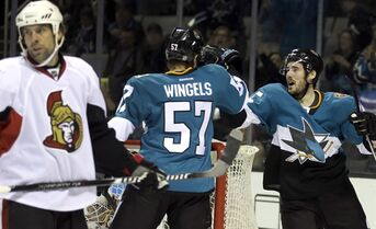 San Jose Sharks' Tommy Wingels (57) celebrates with James Sheppard, right, after Wingels scored a goal against the Ottawa Senators during the first period of an NHL hockey game Saturday, Feb. 28, 2015, in San Jose, Calif. At left is Senators' David Legwand. (AP Photo/Ben Margot)