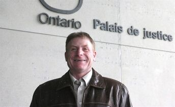 Shawn Drennan, part of a four-family fight against Ontario's wind-turbine legislation, is seen outside court in London, Ont., on Monday, Nov. 17, 2014. A demand that four Ontario families pay hundreds of thousands of dollars in legal costs to billion-dollar companies is a thinly disguised warning to anyone pondering a challenge to industrial wind farms in Ontario, the families say. THE CANADIAN PRESS/Colin Perkel