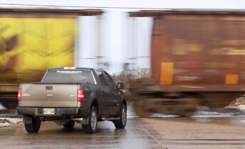 A truck waits for a long train pulling grain cars to pass at Sturgeon Road and Saskatchewan Avenue.