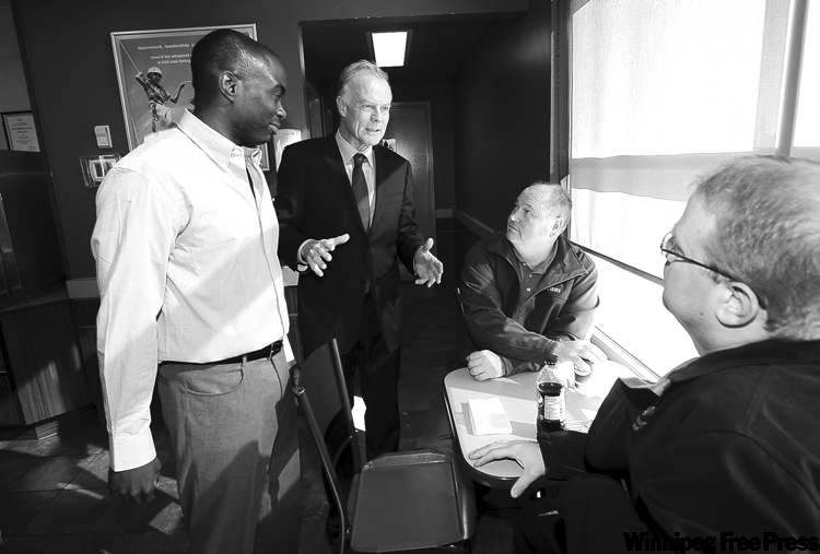 A stoic Liberal Leader Jon Gerrard with Seine River candidate Troy Osiname, talking to (seated, left) Leonard Zirul and Joel Shaw Friday.