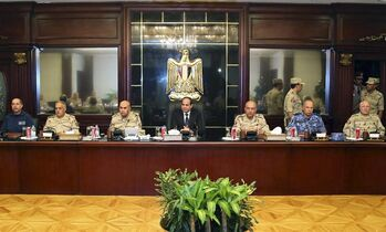 In this photo provided by Egypt's state news agency MENA, Egyptian President Abdel-Fattah el-Sissi, center, meets with top officials and army commanders in an emergency session in Cairo, Egypt, Saturday, Oct. 25, 2014. El-Sissi appeared on the state-run TV and said a deadly assault on an army checkpoint in the Sinai Peninsula that killed 30 troops was a