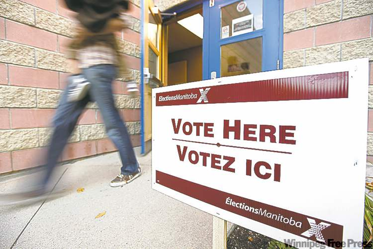 A voter walks out of the polling station after voting in the Manitoba election in Winnipeg, Tuesday.