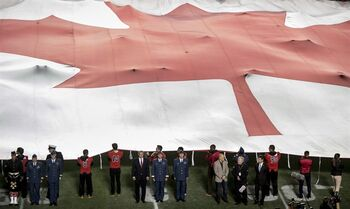 Canadian Prime Minister Stephen Harper, General Tom Lawson, Chief of the Defence Staff of the Canadian Armed Forces, and Chief Warrant Officer Kevin West (Centre right to left) take part in a pre-game ceremony in tribute to the two fallen Canadian Armed Forces members, Warrant Officer Patrice Vincent and Cpl. Nathan Cirillo, before a CFL game in Ottawa on Friday, Oct. 24, 2014. THE CANADIAN PRESS/Justin Tang