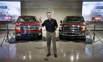 Ford Truck Group Marketing Manager Doug Scott stands between a Ford F-150 truck, left, and the new aluminum-sided 2015 F-150 truck, right, both on scales, at the company's Development Center in Dearborn, Mich., Tuesday, July 22, 2014. The weight difference between the two vehicles is 732 pounds. Ford said its new pickup can keep up with rivals despite its lighter weight. (AP Photo)