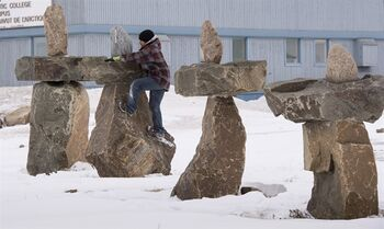 A young boy climbs an inukshuk Thursday, April 23, 2015 in Iqaluit, Nunavut. Ministers from the eight Arctic nations and the leaders of northern indigenous groups will meet Friday at the Arctic Council Ministerial Meeting in Iqualuit. THE CANADIAN PRESS/Paul Chiasson