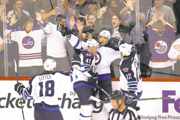 Winnipeg Jets forward Blake Wheeler (26) celebrates his goal with Derek Meech (47), Randy Jones (12) and Bryan Little (18) against the Carolina Hurricanes during third period pre-season NHL action in Winnipeg on Wednesday, September 28, 2011. THE CANADIAN PRESS/John Woods