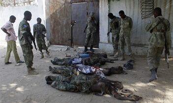 EDS NOTE: GRAPHIC CONTENT - In this photo taken Thursday, Dec. 25, 2014, Somali soldiers and civilian gather around dead bodies of Al-Shabab militants, who attacked AU base Headquarters in Mogadishu, Somalia. Gunmen attacked the African Union's main base in the Somali capital of Mogadishu on Thursday leading to an exchange of gunfire between militants and soldiers that killed at least nine people, including three soldiers, an official with the mission in Somalia said. Three militants were captured during the Christmas day lunch hour attack on the African Union Mission to Somalia's Halane base camp, the group said in a statement. AP Photo/Farah Abdi Warsameh)