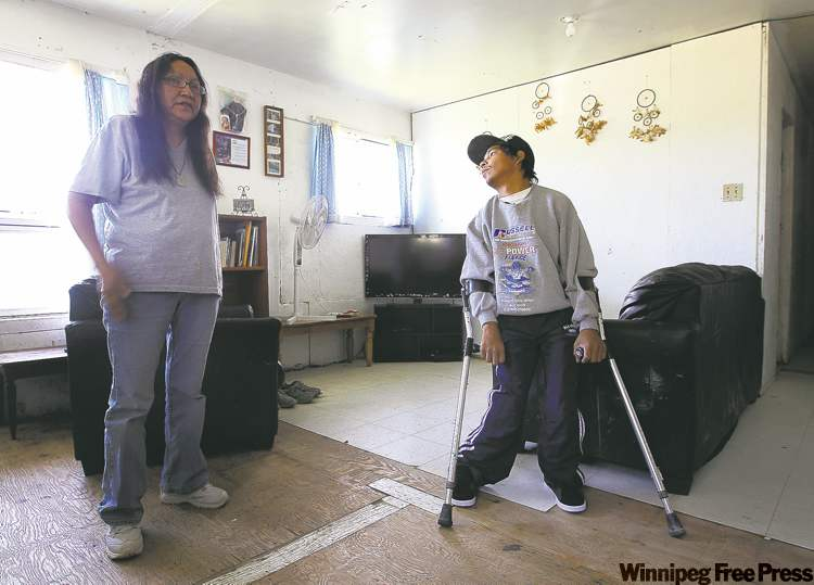 Alice Taylor with her son Kevin,  who has cerebral palsy. She has filed a human rights complaint over the lack of programs for disabled people on the reserve. Below, Kevin Taylor often has to get to the bathroom by crawling.