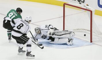 Dallas Stars forward Tyler Seguin (91) scores a goal as Los Angeles Kings goalie Jonathan Quick (32) and defenseman Drew Doughty (8) defend in the second period of an NHL hockey game, Saturday, Nov. 22, 2014, in Dallas. (AP Photo/Brandon Wade)