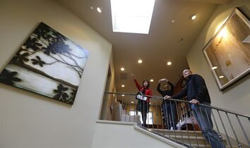 Janie Lee, left, a residential specialist with John L. Scott Real Estate, shows a home for sale to her client, Hongbin Wei, center, of Beijing, China, Thursday, Dec. 18, 2014, in Medina, Wash., near Seattle, as homeowner Doug Ebstyne looks on at right. Real estate agents such as Lee are taking note of growing connections linking China and Washington state, which ranks second to California in real estate sales to Chinese buyers. (AP Photo/Ted S. Warren)