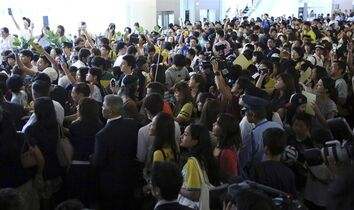 Fans try to see Brazilian Soccer player Neymar at Haneda airport in Tokyo, Thursday, July 31, 2014. Neymar is in Tokyo for several promotional events. (AP Photo/Eugene Hoshiko)