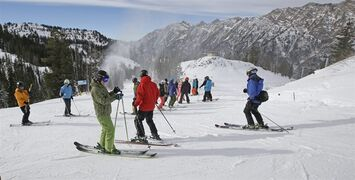 Skiers and snowboarders look on during Snowbird Ski Resort's opening day for the 2014/15 winter season, in Little Cottonwood Canyon in the Wasatch Range Thursday, Nov. 20, 2014, outside of Salt Lake City. Skiers and snowboarders traveling to Utah this winter will find the same jagged mounting peaks looming just east of Salt Lake City and many familiar trails at the state's 15 resorts. (AP Photo/Rick Bowmer)
