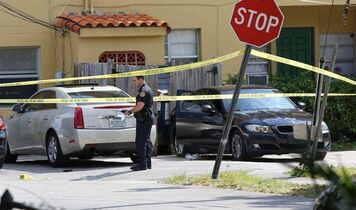 In this photo taken on Monday, March 30, 2015, Miami-Dade police work at a crime scene in Miami, involving the two teenage sons of Roxanne Dube, Canada's counsel general in Miami. (AP Photo/El Nuevo Herald, Hector Gabino) MAGS OUT