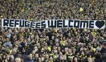 Dortmund supporters hold a banner prior the German first division Bundesliga soccer match between BvB Borussia Dortmund and Hannover 96 in Dortmund, Germany, Saturday, Oct. 25, 2014. (AP Photo/Frank Augstein)
