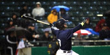 Winnipeg Goldeye Josh Mazzola swings and misses in the pouring rain during a game at Shaw Park against the Lincoln Saltdogs in playoff action.
