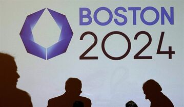 Shadows of organizers and reporters pass a video display screen prior to a news conference by organizers of Boston's campaign for the 2024 Summer Olympics in Boston, Wednesday, Jan. 21, 2015. The organizers released their