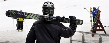In this photo taken Saturday April 25, 2015 a skier heads to the slopes at Wildcat ski area in Gorham, N.H. The ski season has stretched longer into spring than it has in recent years, due to a deep base of snow and unseasonably cold spring. (AP Photo/Jim Cole)