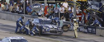 Jimmie Johnson makes a pit stop during the NASCAR Sprint Cup championship series auto race, Sunday, Nov. 16, 2014, in Homestead, Fla. (AP Photo/David Graham)